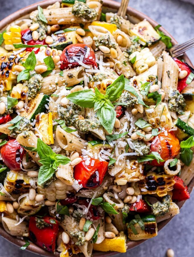 Overhead photo of Serving bowl filled with grilled zucchini, summer squash, tomatoes, corn and pasta. Coated in pesto and garnished with basil, parmesan cheese and pine nuts.