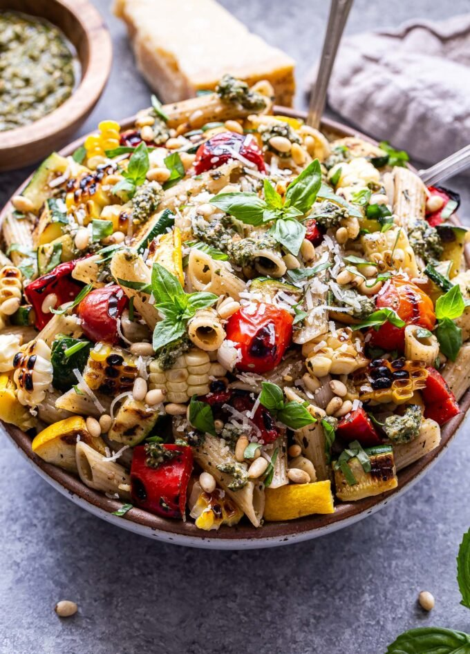 Serving bowl filled with grilled zucchini, summer squash, tomatoes, corn and pasta. Coated in pesto and garnished with basil, parmesan cheese and pine nuts.