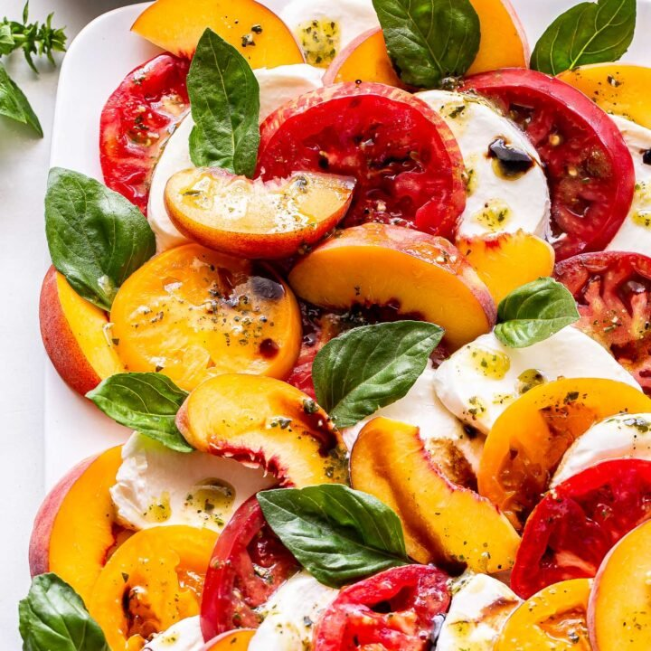 Overhead photo of Peach Tomato Caprese Salad with basil and fresh mozzarella on a white rectangular plate and a small bowl of lemon pesto vinaigrette behind it.