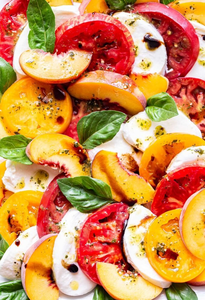 Closeup photo of Peach Tomato Caprese Salad with basil and fresh mozzarella.
