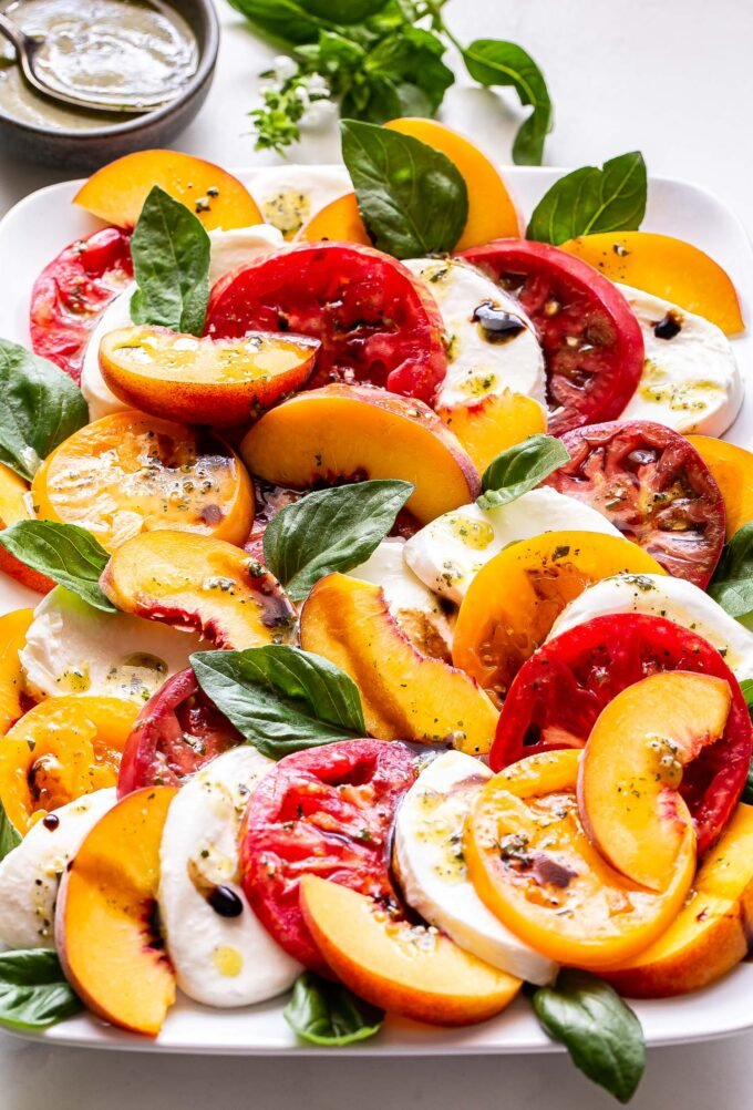 Peach Tomato Caprese Salad with basil and fresh mozzarella on a white rectangular plate and a small bowl of lemon pesto vinaigrette behind it.