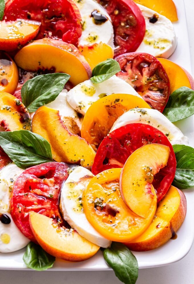 Peach Tomato Caprese Salad with basil and fresh mozzarella on a white rectangular plate.
