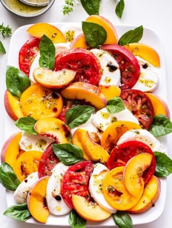 Overhead photo of Peach Tomato Caprese Salad with basil and fresh mozzarella on a white rectangular plate and a small bowl of lemon pesto vinaigrette behind it.