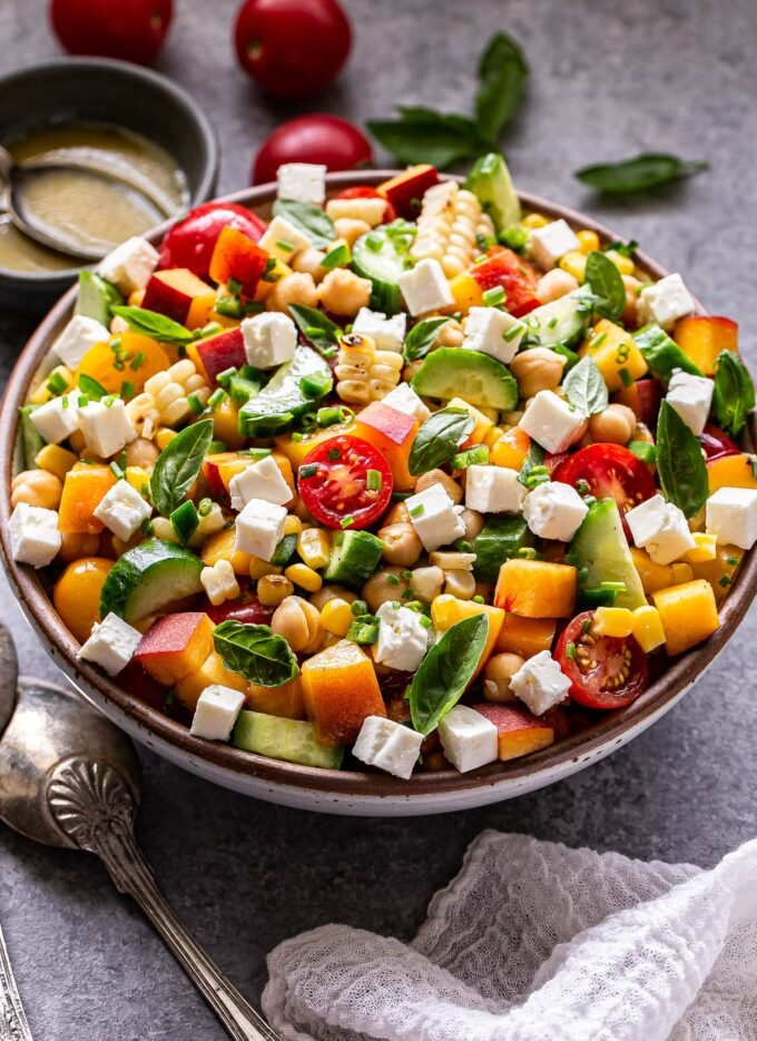 Front facing photo of chickpea, cucumber, tomato, peach, feta, basil salad in serving bowl with a small bowl of lemon vinaigrette behind it. Serving spoons on the left side of the salad bowl.
