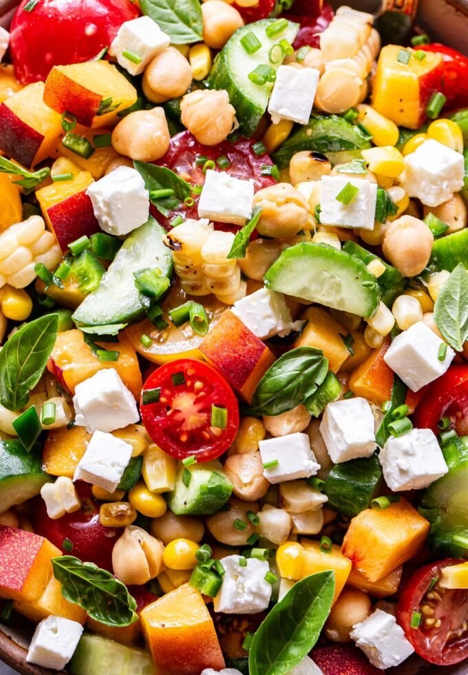 Closeup photo of chickpea, cucumber, tomato, peach, feta, basil salad.