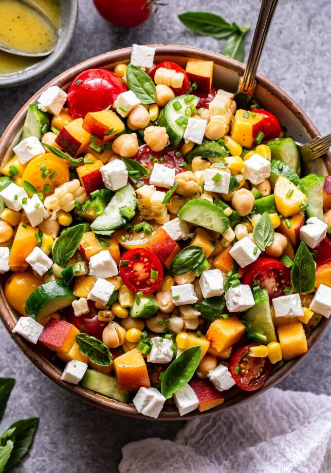 Overhead photo of chickpea, cucumber, tomato, peach, feta, basil salad in serving bowl with spoons in the bowl. A small bowl of lemon vinaigrette behind the salad.