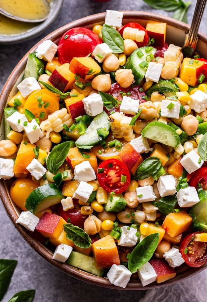 Overhead photo of chickpea, cucumber, tomato, peach, feta, basil salad in serving bowl with a small bowl of lemon vinaigrette behind it.