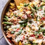 Ground turkey, zucchini, summer squash, green beans and tomatoes topped with melted mozzarella cheese in metal skillet with a wooden spoon in the skillet.