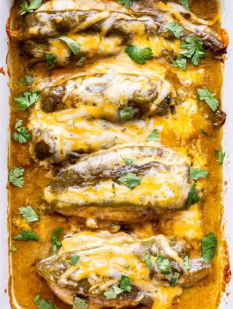Overhead photo of four chicken breasts in a white rectangular casserole dish. Chicken is baked and covered with green chiles, melted cheese and green enchilada sauce.