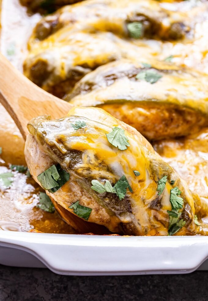 Wooden spatula scooping out a baked green chile chicken breast topped with melted cheese out of a white casserole dish.
