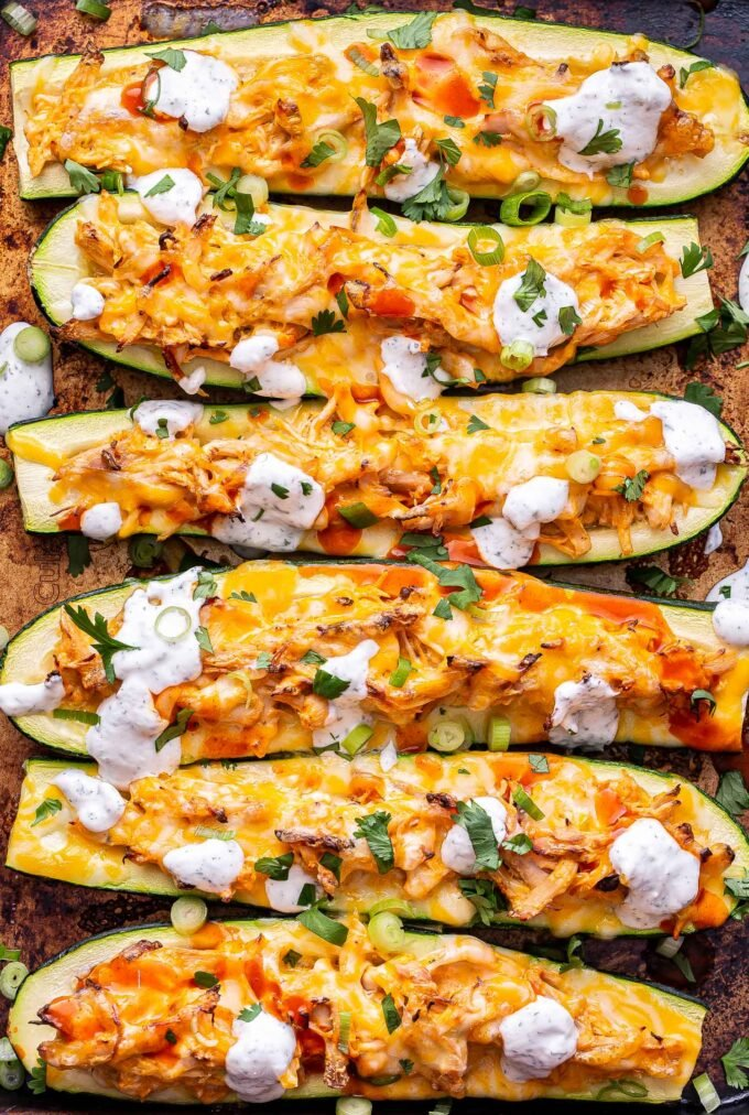 Overhead photo of sheet pan with 6 zucchini halves filled with buffalo chicken, topped with melted cheese, ranch dressing, green onions and cilantro.