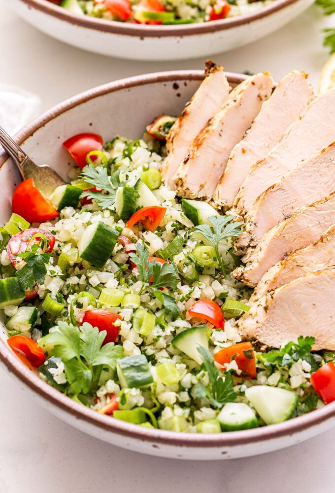 Sliced Greek Lemon Grilled Chicken on top of Cauliflower Tabbouleh in a white bowl with a fork in the bowl.