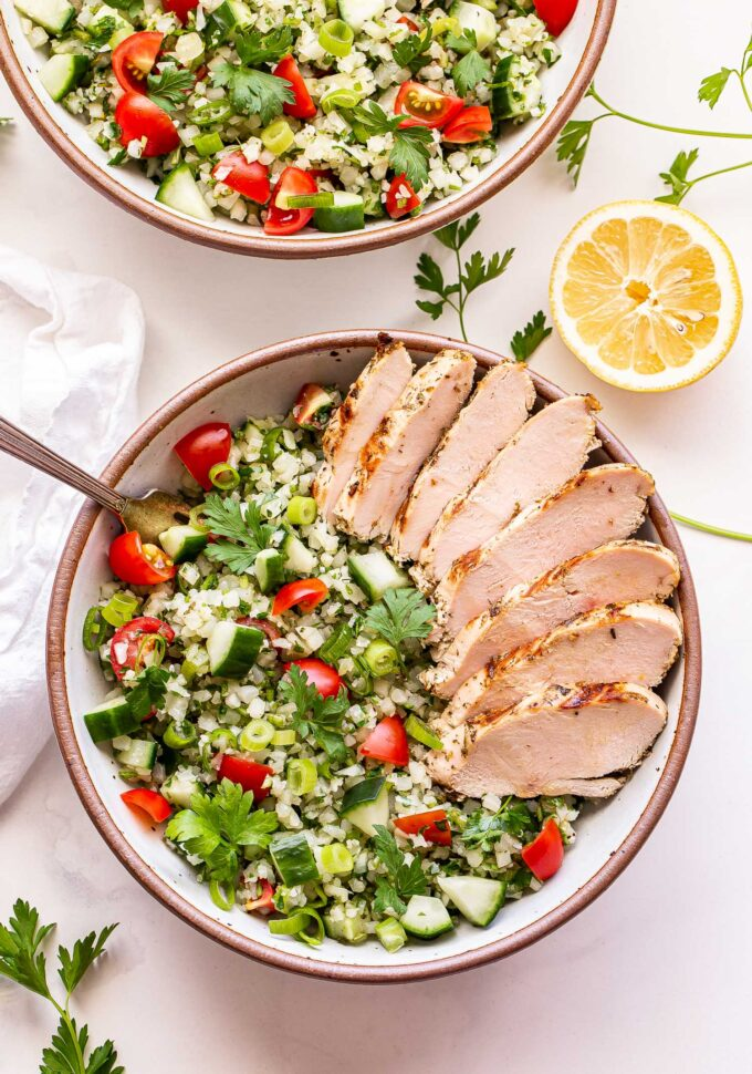 Overhead photo of Sliced Greek Lemon Grilled Chicken on top of Cauliflower Tabbouleh in a white bowl. A second bowl of the tabbouleh is behind the first one along with a half of a lemon.