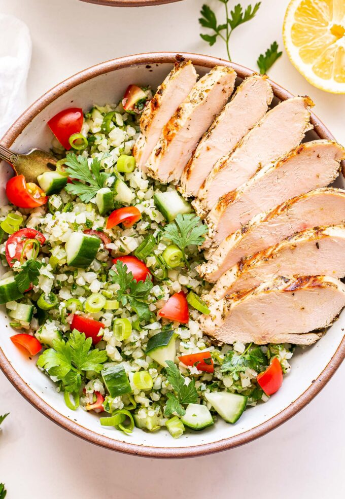 Overhead photo of Sliced Greek Lemon Grilled Chicken on top of Cauliflower Tabbouleh in a white bowl. Half of a lemon behind the bowl.