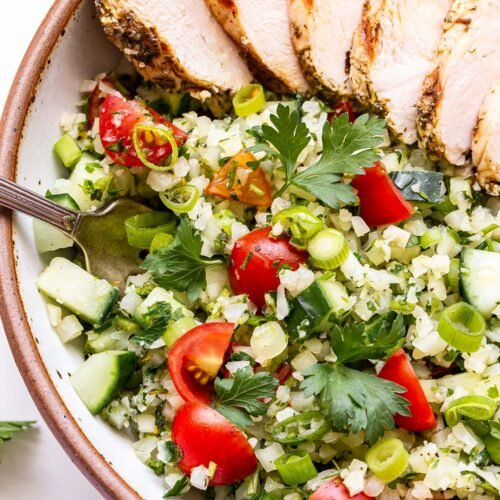 Overhead photo of Sliced Greek Lemon Grilled Chicken on top of Cauliflower Tabbouleh in a white bowl.