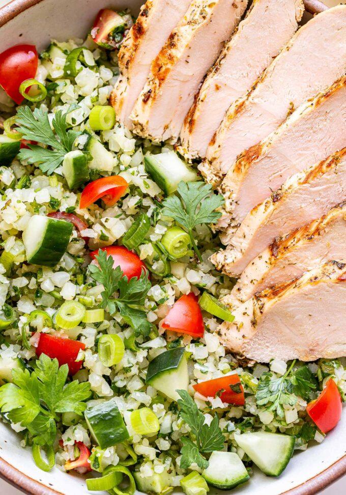 Closeup photo of sliced Greek Lemon Grilled Chicken on top of Cauliflower Tabbouleh salad