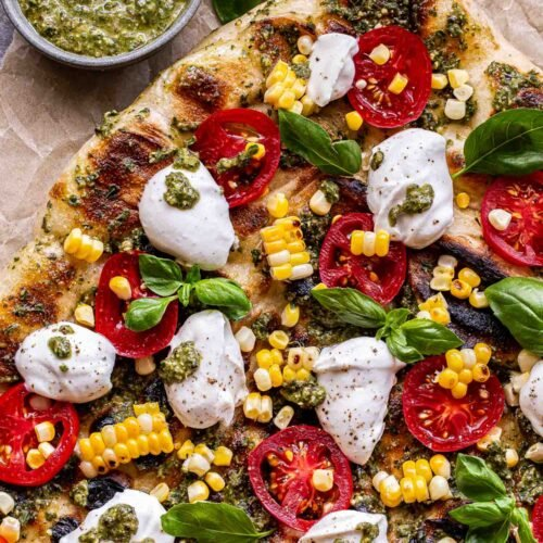 Overhead photo of Grilled Corn, Tomato and Pesto Pizza with dollops of ricotta and fresh basil leaves. A small bowl of pesto and basil leaves behind the pizza.