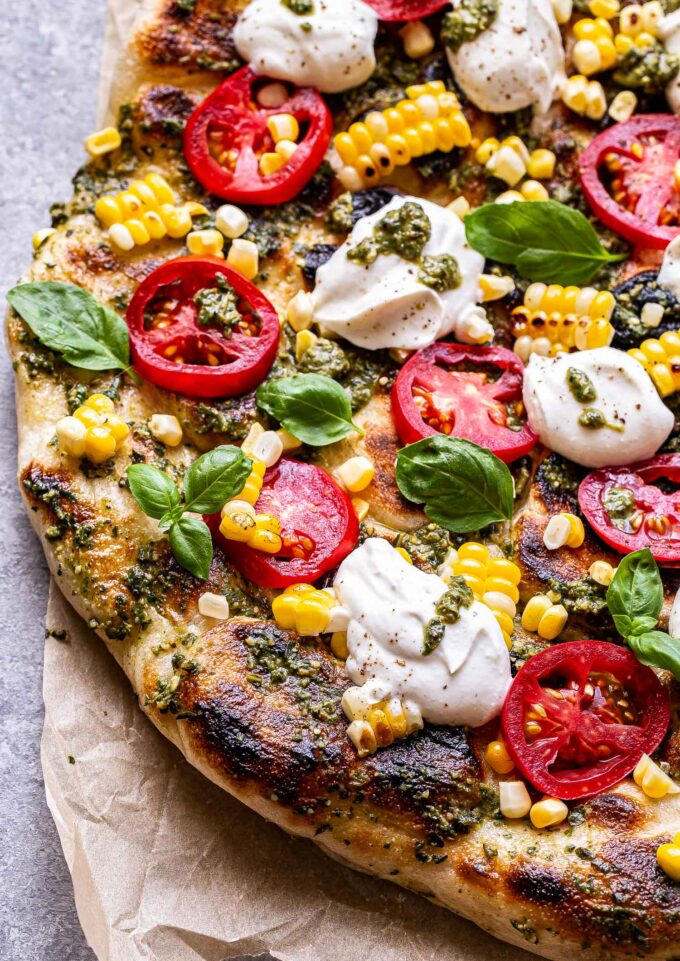 Overhead photo of Grilled Corn, Tomato and Pesto Pizza with dollops of ricotta and fresh basil leaves.