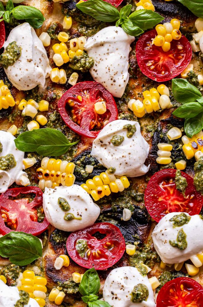 Closeup photo of Grilled Corn, Tomato and Pesto Pizza with dollops of ricotta and fresh basil.