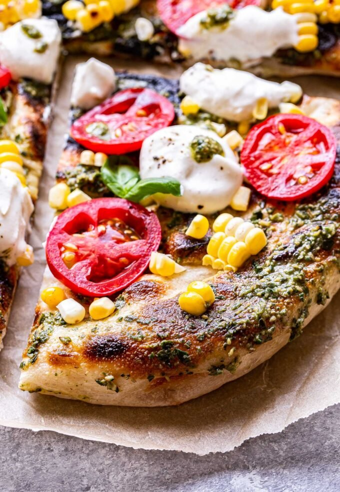 Closeup photo of a corner slices of Grilled Corn, Tomato and Pesto Pizza with dollops of ricotta cheese and fresh basil.