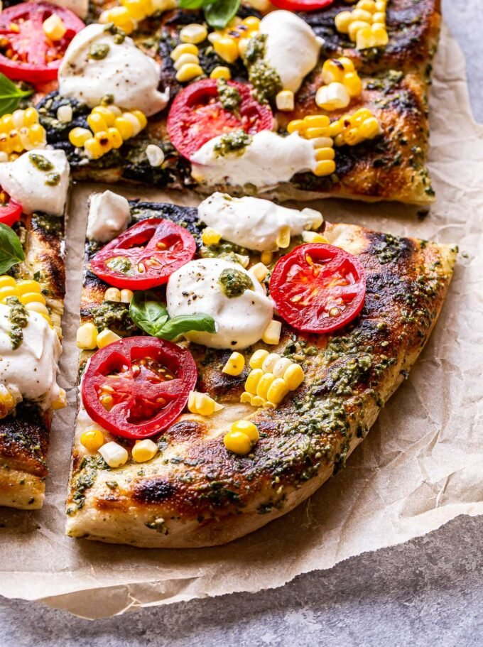 Overhead photo of a corner slice of Grilled Corn, Tomato and Pesto Pizza with dollops of ricotta and basil leaves.