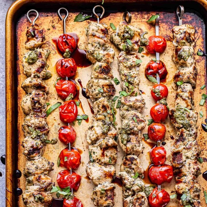 Overhead photo of four grilled pesto chicken skewers and two grilled tomato skewers on a sheet pan. Basil leaves and a bowl of pesto behind the sheet pan.