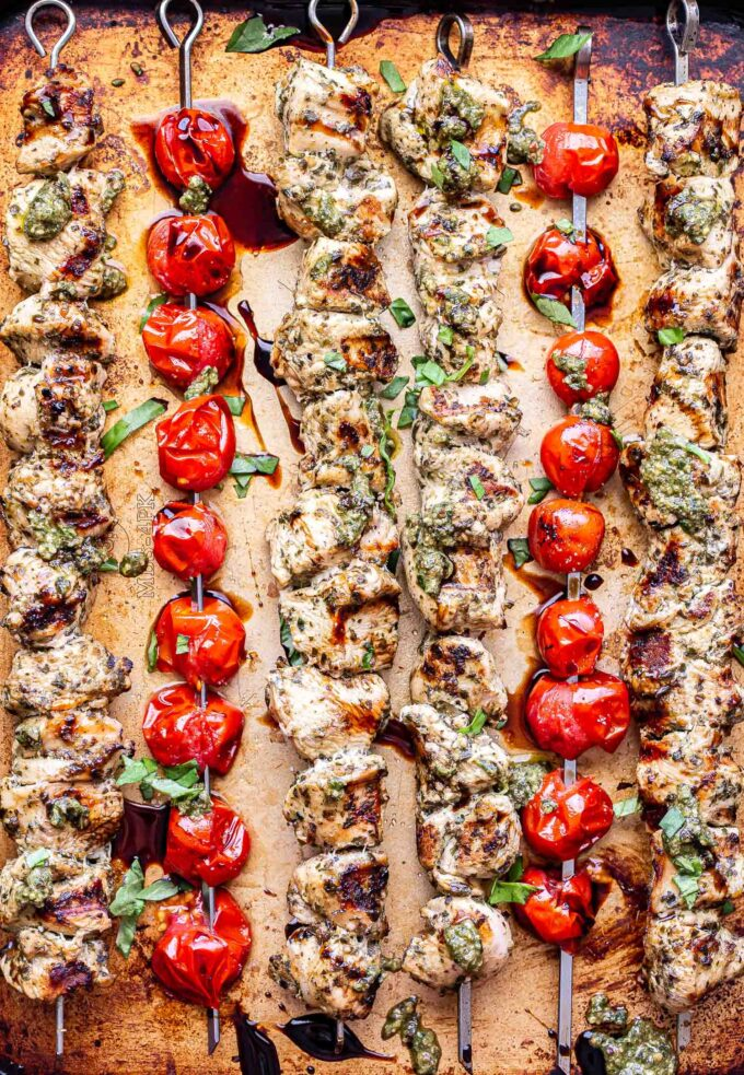 Overhead photo of four Grilled Pesto Chicken Skewers and two tomato skewers on a sheet pan.