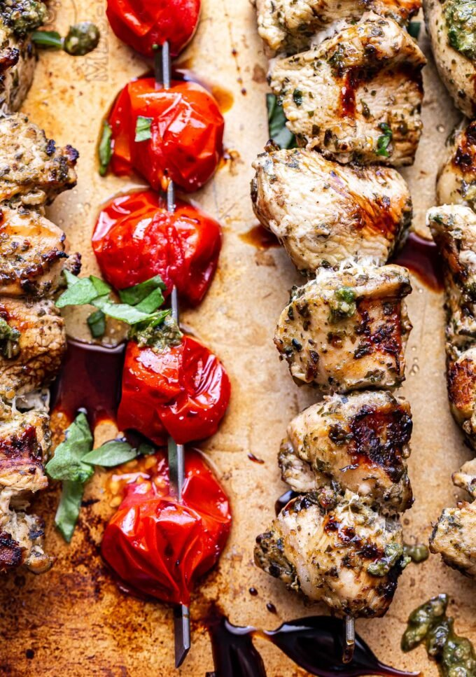 Closeup photo of grilled pesto chicken skewers and a grilled tomato skewer on a sheet pan drizzled with balsamic glaze.