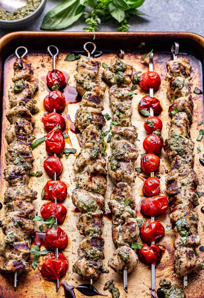 Grilled Pesto Chicken and tomato skewers on a sheet pan.