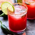 Spicy Watermelon Margarita in a tumbler style glass lined with chili lime salt and a lime wedge.