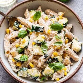 Overhead photo of a white bowl filled with penne pasta, zucchini, corn, basil leaves and a creamy ricotta sauce. There is a fork in the bowl and a glass of white wine behind the bowl.