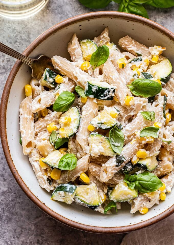 Overhead photo of a white bowl filled with penne pasta, zucchini, corn, basil leaves and a creamy ricotta sauce.