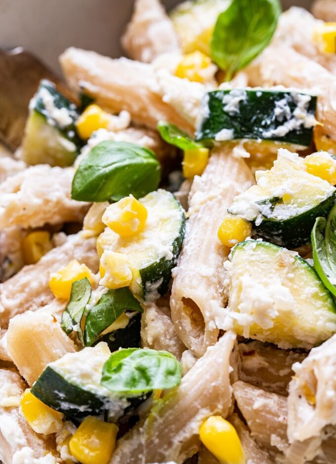 Closeup photo of penne pasta with zucchini, corn and basil in a creamy ricotta sauce.