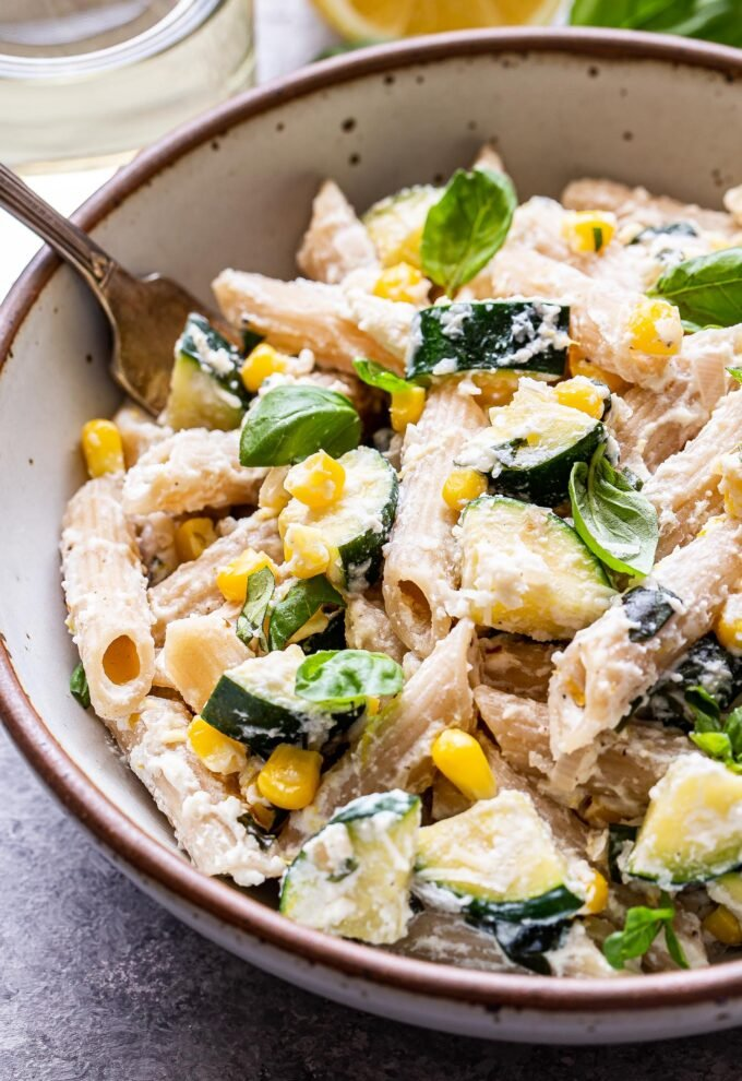 White bowl filled with Zucchini Lemon Basil Ricotta penne Pasta with corn. Fork in the bowl.