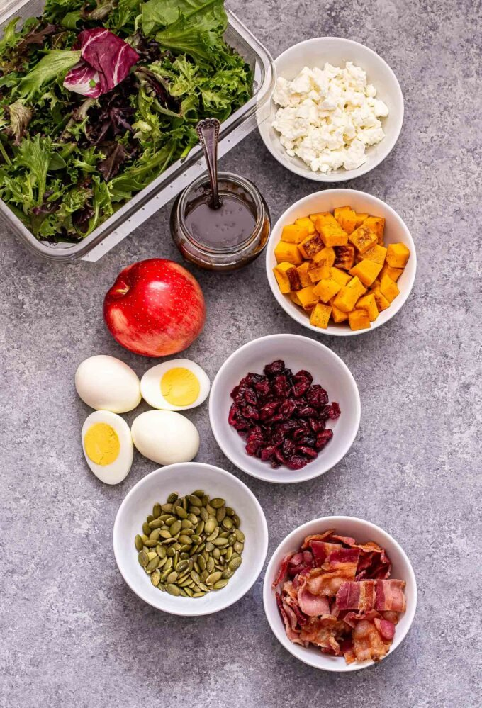 Fall Cobb Salad ingredients photo. White bowls filled with butternut squash, goat cheese, cranberries, pepitas, bacon. Hard boiled eggs, apple, box of mixed greens and a jar of vinaigrette next to the bowls.