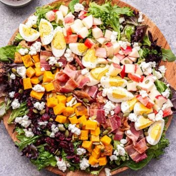 Overhead photo of fall cobb salad on a round wooden platter. Bowl of maple balsamic vinaigrette behind the salad.