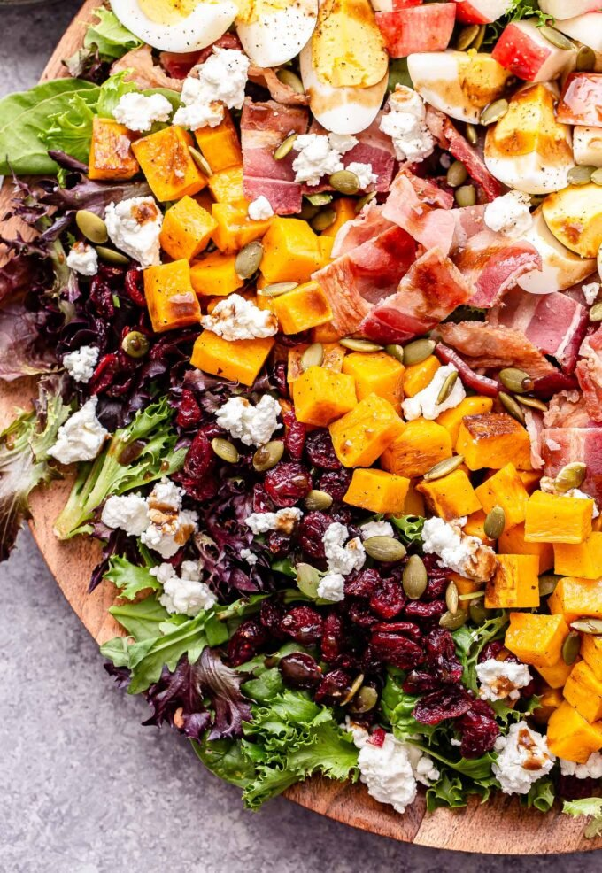 Overhead photo of fall cobb salad on a round wooden platter. Salad is topped with dried cranberries, pepitas, butternut squash, bacon, hard boiled eggs, apples and crumbled goat cheese.