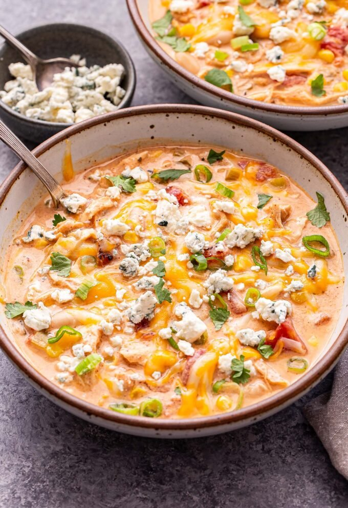 Overhead photo of Buffalo Chicken Chili in two white bowl with a spoons in the bowls. Chili is topped with melted cheese, blue cheese crumbles, green onions and cilantro. A small bowl of blue cheese crumbles is behind the bowl in the front.