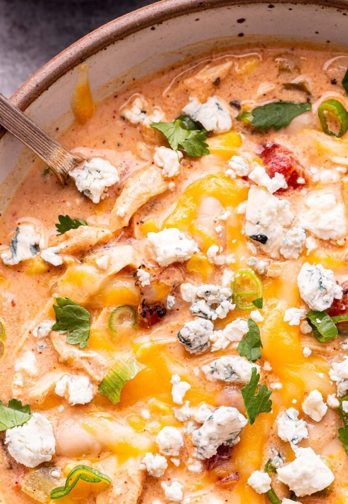 Closeup overhead photo of Buffalo Chicken Chili in a white bowl with a spoon in the bowl. Chili is topped with melted cheese, blue cheese crumbles, green onions and cilantro.