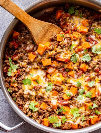 Overhead photo of a metal skillet filled with ground beef, tomatoes, sweet potatoes, southwest spices and topped with melted cheese and cilantro. Wooden serving spoon in the skillet.