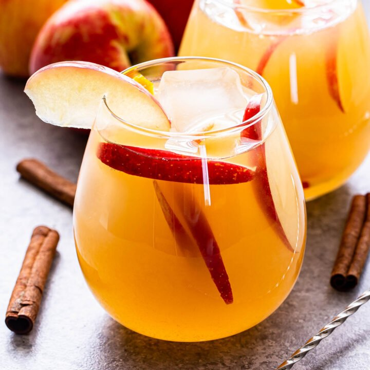 Front view of two glasses filled with apple cider sangria. Apple slices are in the cocktails and the rims of the glasses have an apple slice for garnish. Apples and cinnamon sticks are surrounding the glasses.