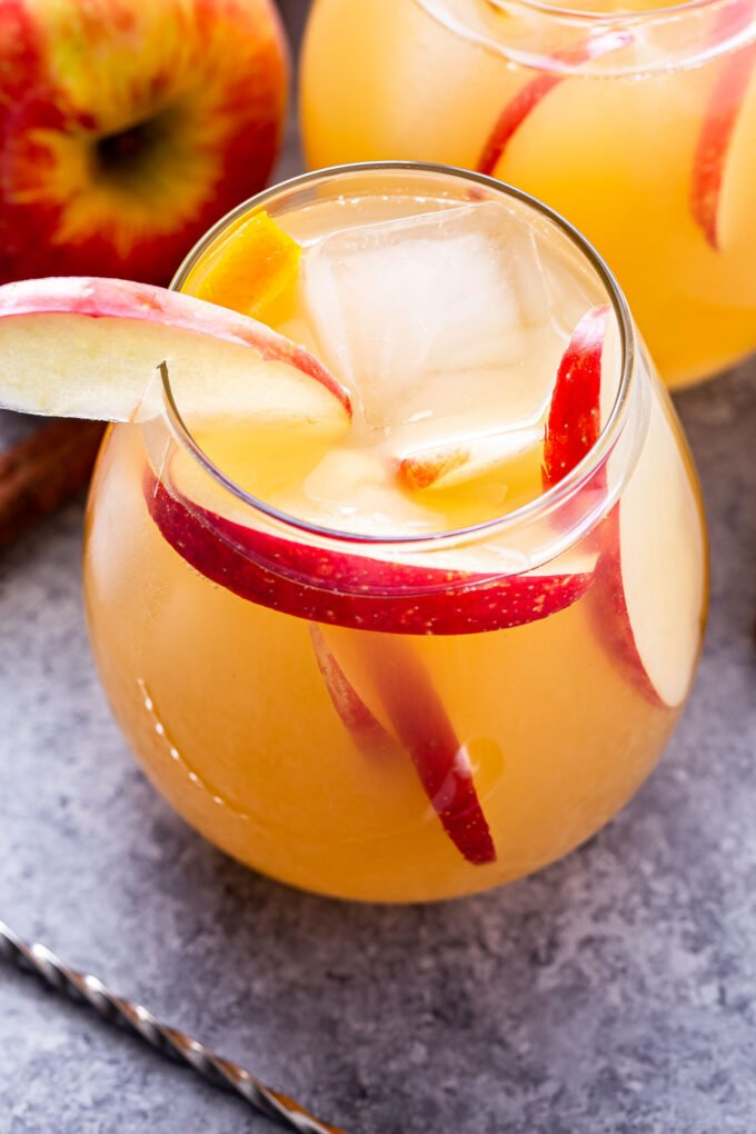 Closeup overhead photo of a glass of apple cider sangria with apple slices in it and an apple slice of the rim of the glass.