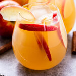 Front view of a glass filled with apple cider sangria. Apple slices are in the cocktail and the rim of the glass has an apple slice for garnish.
