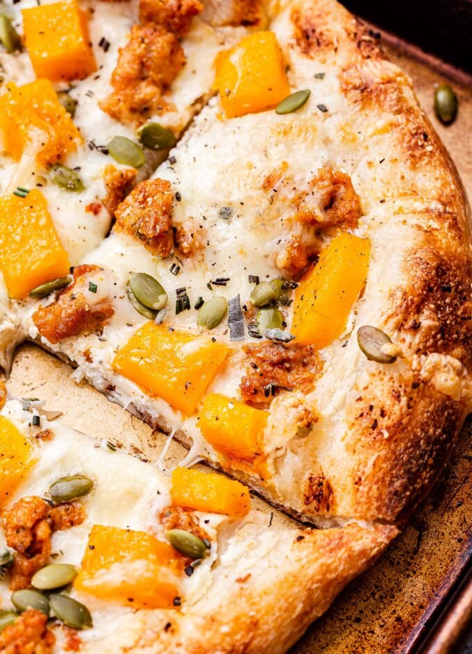 A corner slice of the Butternut Squash Sausage and Ricotta Pizza.