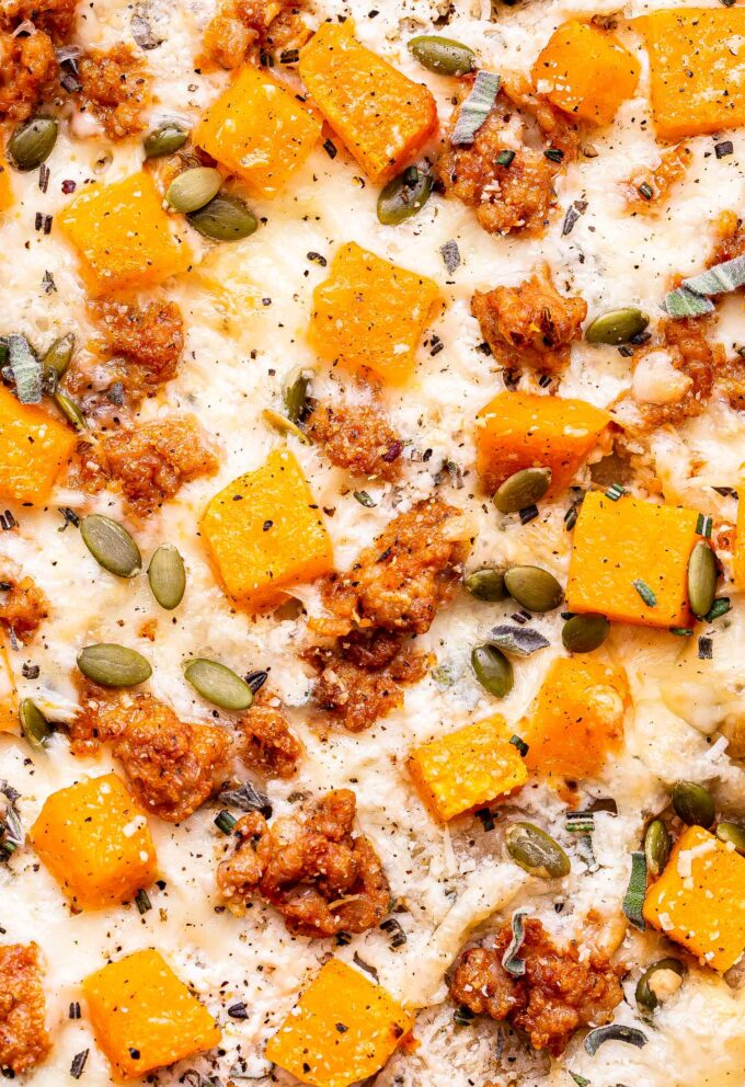 Closeup overhead photo of the pizza topped with roasted butternut squash, crumbled sausage, pepitas, melted cheese and chopped herbs.