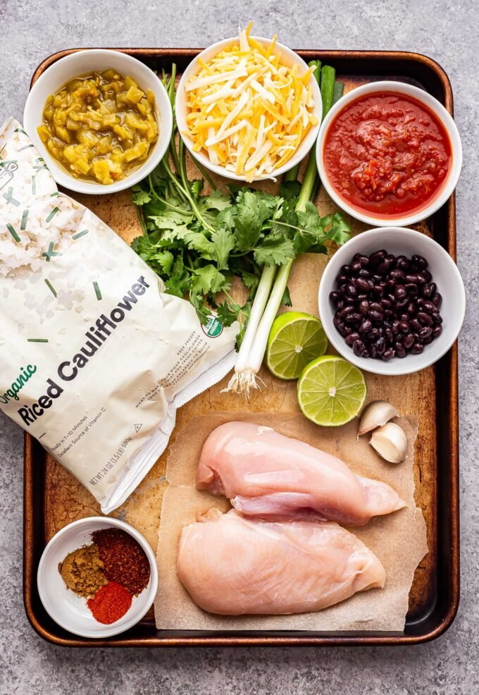 Ingredients for the salsa chicken and cauliflower rice on a sheet pan. chicken breasts, spices, lime, garlic, black beans, salsa, green chiles, cauliflower rice and cheese.