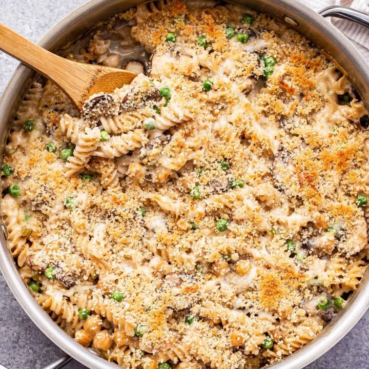 Overhead photo of Chickpea Noodle Casserole in a metal skillet with a wooden spoon in it.