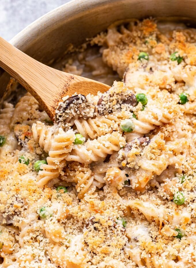 Closeup photo of a wooden spoon scooping up some of the Chickpea Noodle Casserole from the metal skillet.