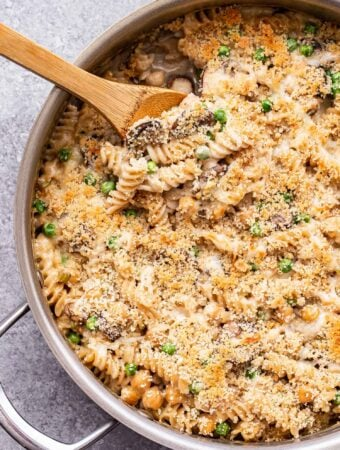 Creamy Chickpea Noodle Casserole with a breadcrumb topping in a metal skillet with a wooden spoon in the skillet.