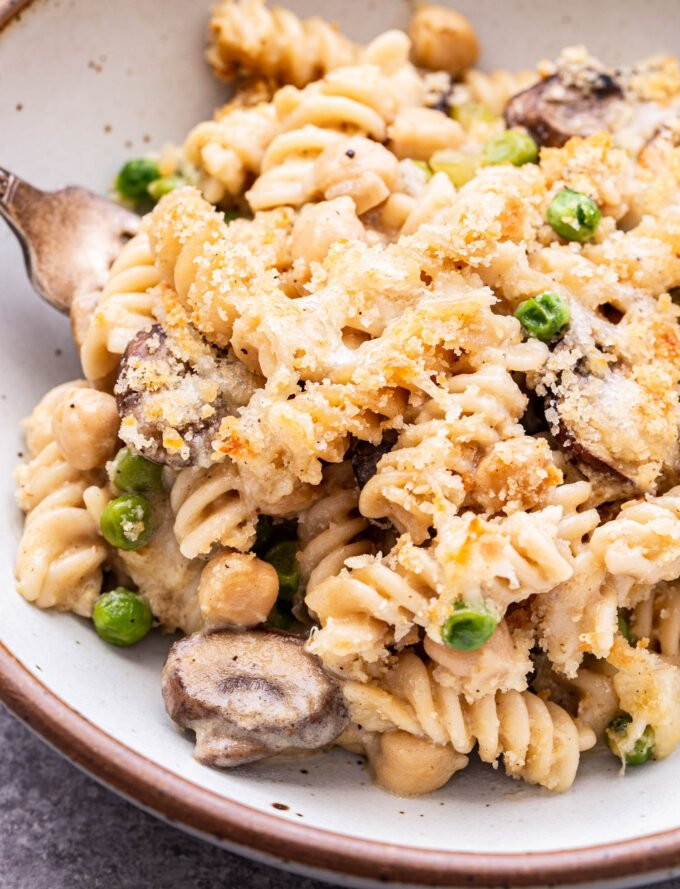 Closeup photo of a serving of Chickpea Noodle Casserole in a white bowl. Casserole has rotini noodles, mushrooms, peas and chickpeas in it and a breadcrumb topping.